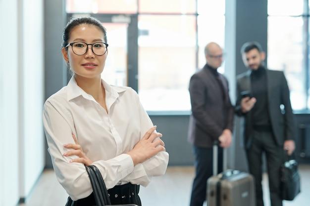 Jovem viajante de negócios de sucesso com uma bolsa pendurada nos braços cruzados com dois homens interagindo