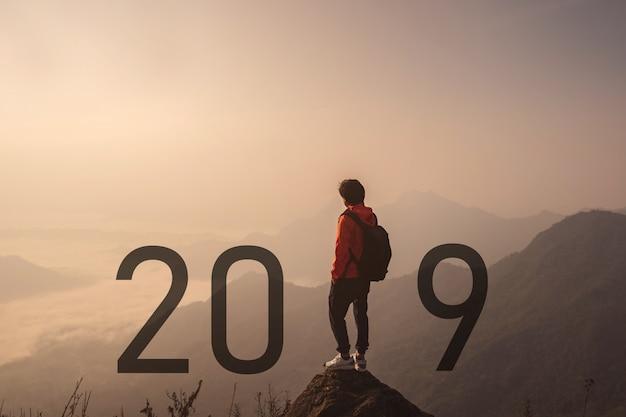 Jovem viajante de pé e olhando a bela paisagem no topo da montanha