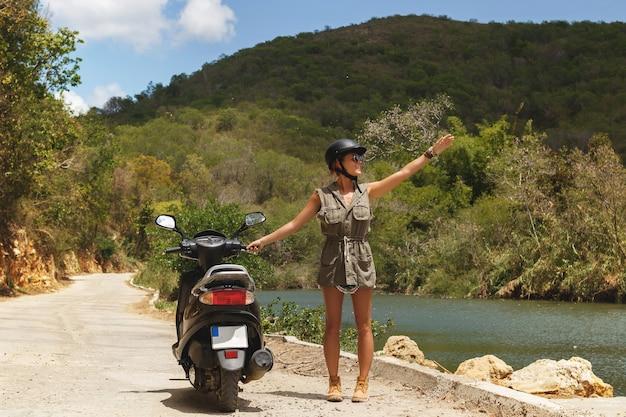 Jovem viajante e scooter na velha estrada rural nas montanhas