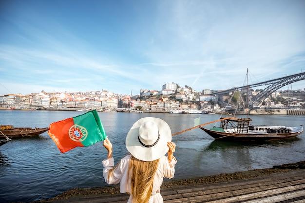 Jovem viajante em pé com a bandeira portuguesa, apreciando a bela vista da cidade no rio douro e os barcos durante a luz da manhã no porto, portugal