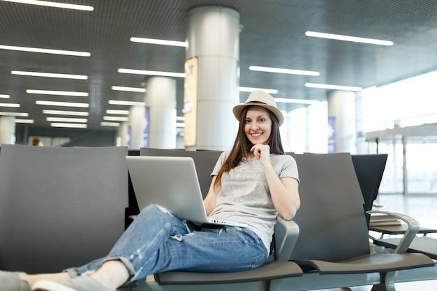 Jovem viajante encantadora mulher de chapéu trabalhando em um laptop enquanto espera no saguão do aeroporto internacional