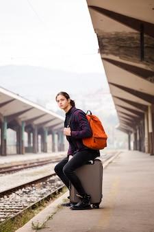 Jovem viajante esperando na estação ferroviária