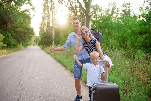Jovem viajante familiar pegando carona em caminhadas em uma estrada vazia.