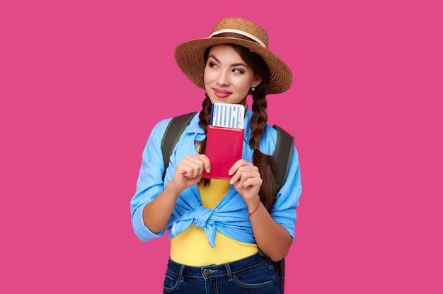 Jovem viajante feminina vestindo roupas casuais e chapéu de palha, segurando o passaporte com bilhete no fundo rosa isolado. conceito de turismo. foto de estúdio