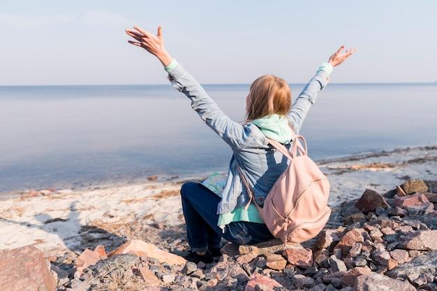 Jovem viajante feminino sentado na praia, levantando os braços com vista para o mar