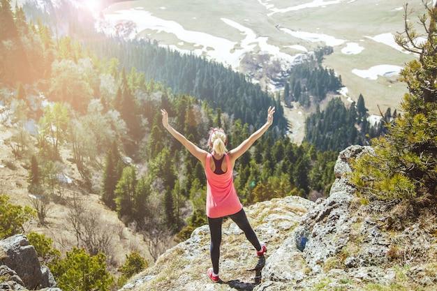 Jovem viajante fica no topo da montanha, com os braços estendidos ... a garota adora viajar.