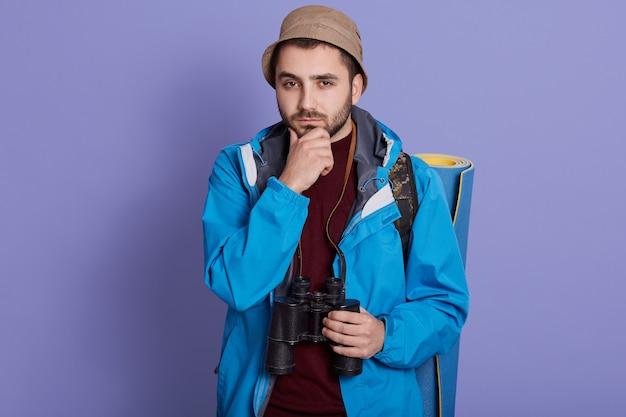 Jovem viajante homem caucasiano confuso, sente-se em dúvida e inseguro, posando contra uma parede azul com mochila e binóculo