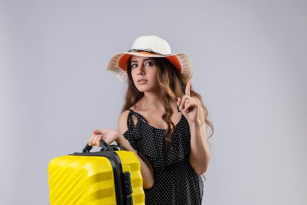 Jovem viajante linda em um vestido de bolinhas com chapéu de verão segurando uma mala de pé com o dedo apontando para cima, concentrada em uma tarefa em pé sobre um fundo branco