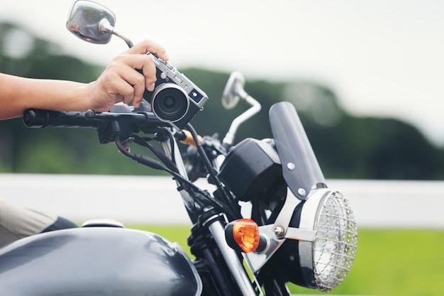 Jovem viajante masculino asiático e fotógrafo sentado na moto de estilo clássico, segurando a câmera