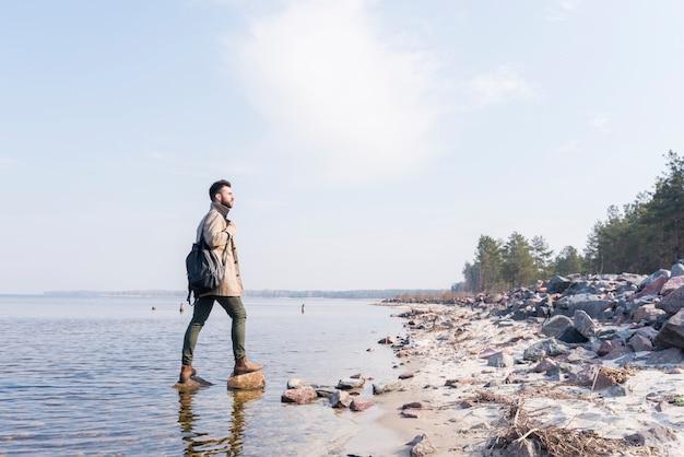 Jovem viajante masculino com é mochila olhando a vista