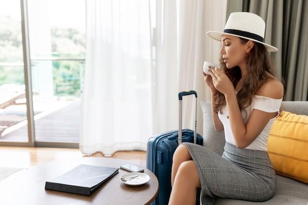 Jovem viajante-mulher de chapéu, bebendo café com bagagem, sentado no quarto de hotel, linda mulher esperando relaxante após a chegada, viajando a negócios com malas de viagem