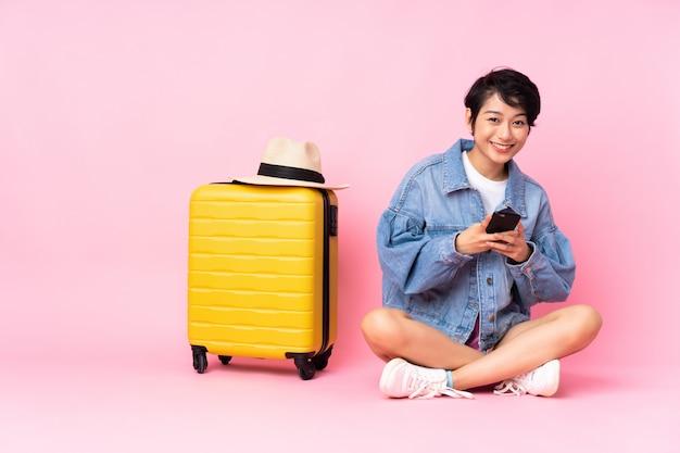 Jovem viajante mulher vietnamita com mala sentado no chão parede rosa, enviando uma mensagem com o celular