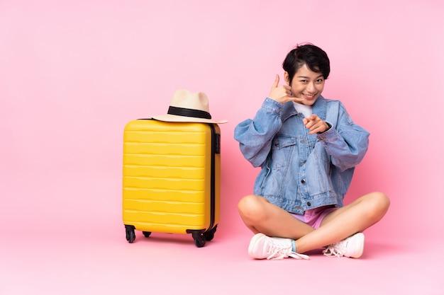 Jovem viajante mulher vietnamita com mala sentado no chão parede rosa fazendo gesto de telefone e apontando a frente