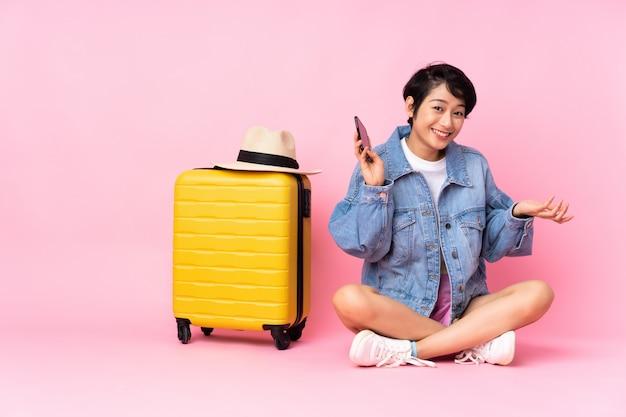 Jovem viajante mulher vietnamita com mala sentado no chão parede rosa mantendo uma conversa com o telefone móvel com alguém