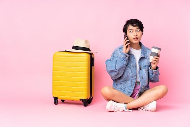 Jovem viajante mulher vietnamita com mala sentado no chão parede rosa segurando café para tirar e um celular