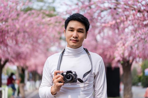 Jovem viajante olhando flores de cerejeira ou flor de sakura desabrochando e segurando uma câmera para tirar uma foto no parque