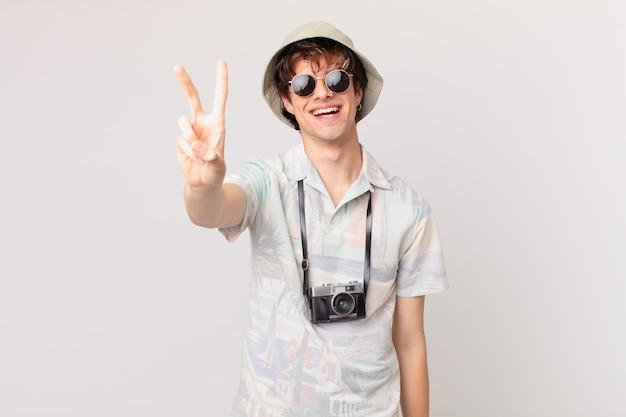 Jovem viajante ou turista sorrindo e parecendo amigável, mostrando o número dois
