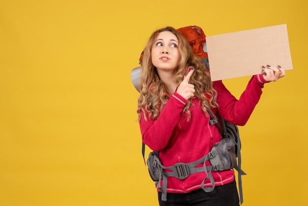 Jovem viajante pegando sua bagagem e apontando um espaço livre para escrever