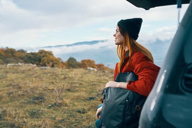 Jovem viajante perto do carro no outono nas montanhas
