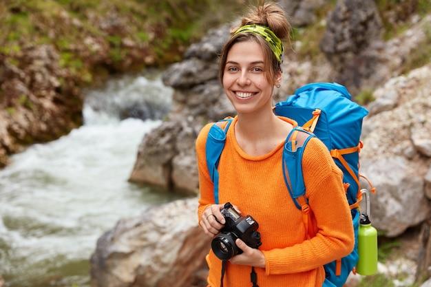 Jovem viajante positivo posa com câmera e mochila contra o desfiladeiro, aprecia a natureza e a paisagem
