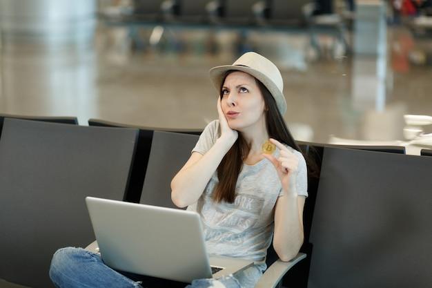 Jovem viajante preocupada, turista, trabalhando em um laptop segurando bitcoin, pensando e mantendo a mão perto do rosto, espere no saguão do aeroporto