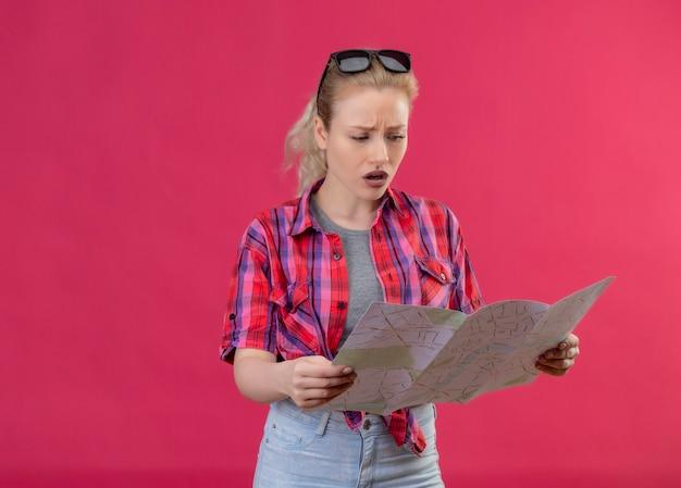 Jovem viajante preocupada, vestindo camisa vermelha e óculos na cabeça, olhando para o mapa na parede rosa isolada