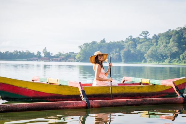 Jovem viajante remando em um barco de madeira em pura ulun danu bratan