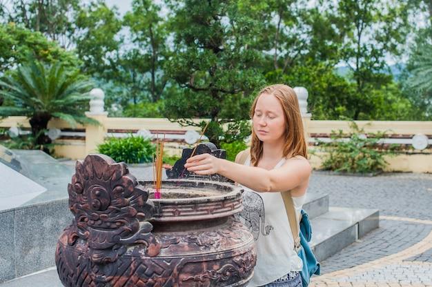 Jovem viajante rezando em ação educada com paus de incenso no templo de budismo no vietnã