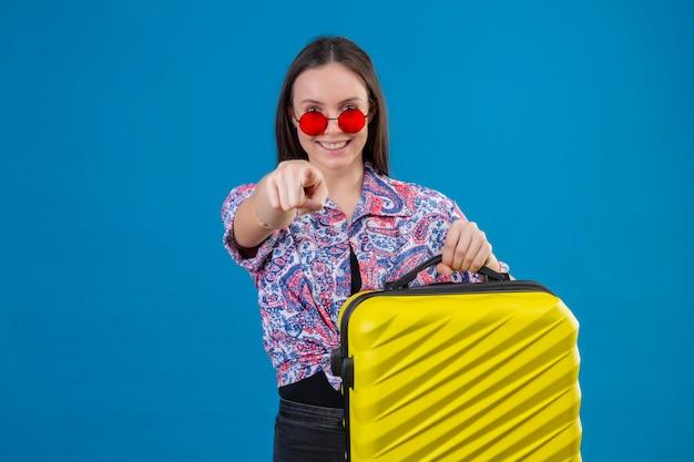 Jovem viajante satisfeita com óculos de sol vermelhos segurando uma mala amarela apontando com o dedo para a câmera e sorrindo alegremente em pé sobre um fundo azul