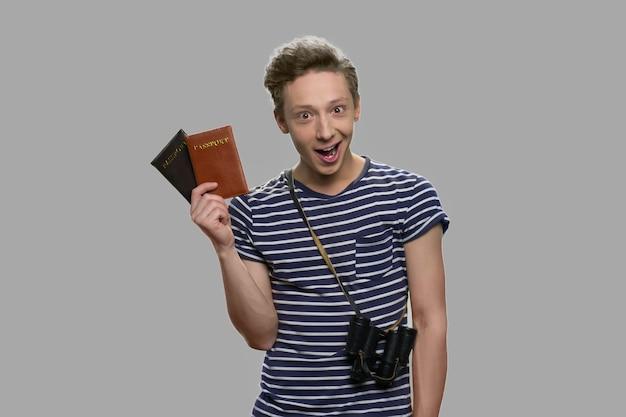 Jovem viajante segurando carteiras de identidade. menino adolescente animado feliz segurando documentos pessoais. obtenha o conceito de visto.