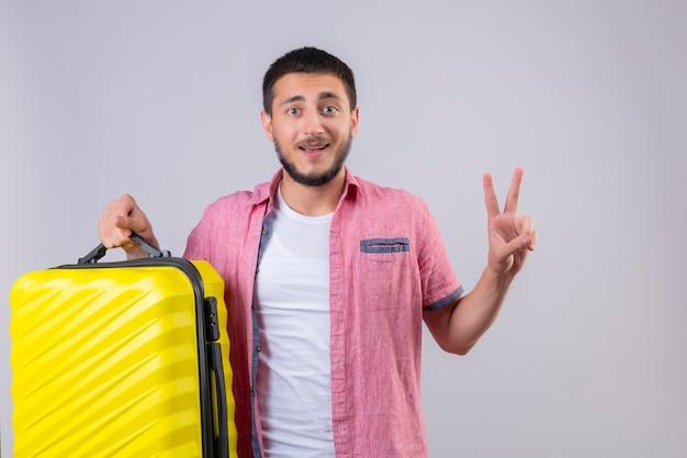 Jovem viajante segurando uma mala, olhando para a câmera, sorrindo, feliz e positivo, mostrando o número dois ou o sinal da vitória em pé sobre um fundo branco