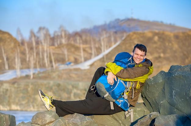 Jovem viajante sentado nas pedras com uma mochila e sorrindo