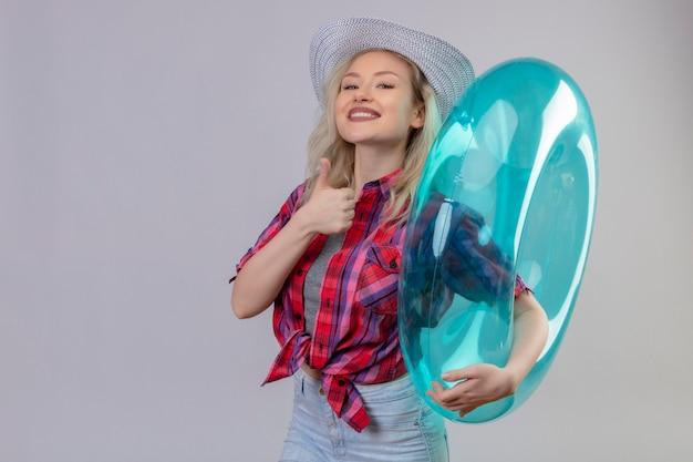 Jovem viajante sorridente com camisa vermelha e chapéu segurando o anel inflável e o polegar levantado sobre fundo branco isolado