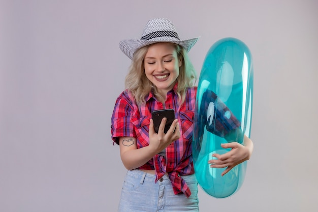 Jovem viajante sorridente com camisa vermelha e chapéu segurando um anel inflável e olhando para o telefone em fundo branco isolado