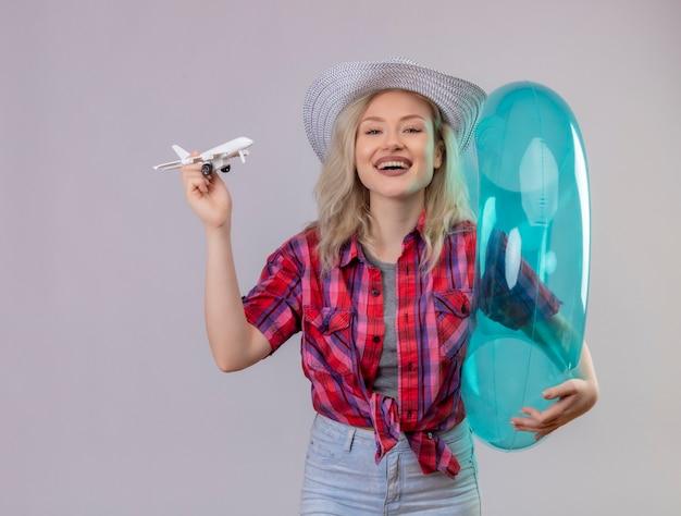 Jovem viajante sorridente com camisa vermelha e chapéu segurando um anel inflável e um plano de brinquedo em fundo branco isolado