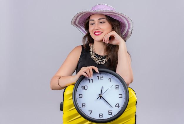 Jovem viajante sorridente usando camiseta preta e chapéu segurando suicase e um relógio de parede no fundo branco