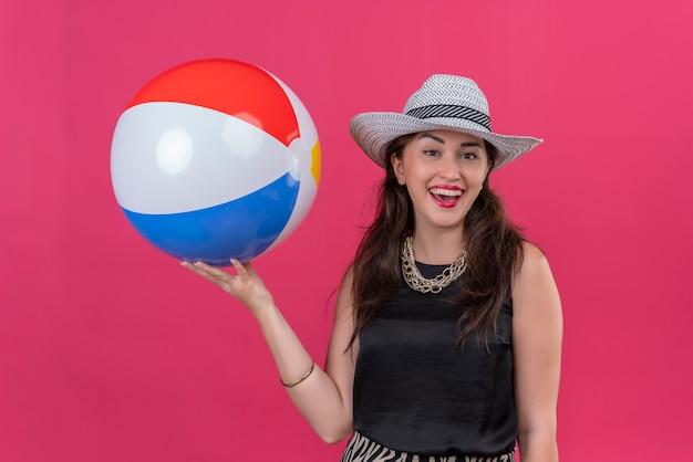 Jovem viajante sorridente usando camiseta preta e chapéu segurando uma bola inflável sobre fundo vermelho