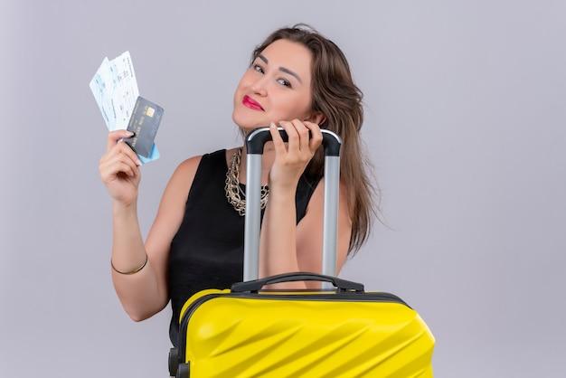 Jovem viajante sorridente, vestindo camiseta preta, segurando as passagens e o cartão de crédito na parede branca