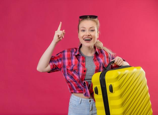 Jovem viajante sorridente, vestindo uma camisa vermelha de óculos, segurando a mala apontando para cima na parede rosa isolada