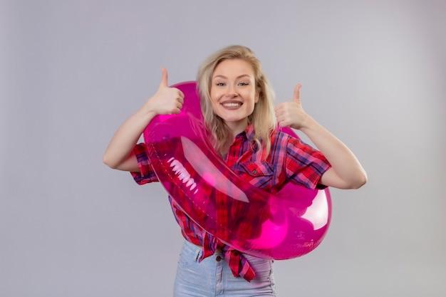 Jovem viajante sorridente, vestindo uma camisa vermelha em um anel inflável, com os polegares para cima em um fundo branco isolado