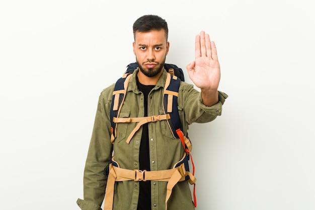 Jovem viajante sul-asiático em pé com a mão estendida, mostrando o sinal de pare, impedindo você.