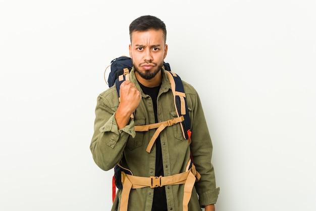 Jovem viajante sul-asiático mostrando punho, expressão facial agressiva.