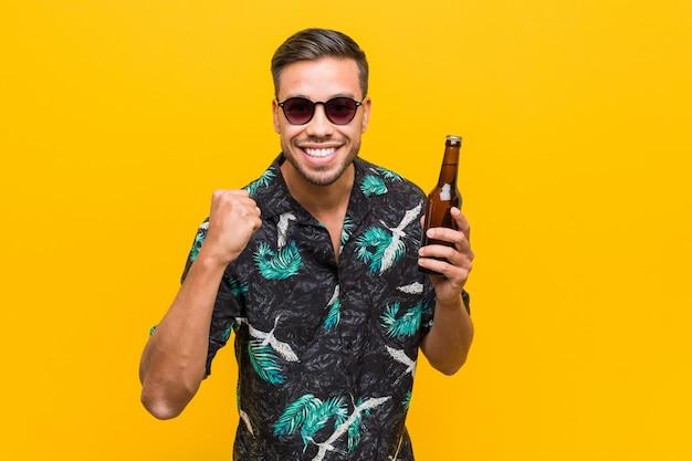 Jovem viajante sul-asiático segurando uma garrafa de cerveja.