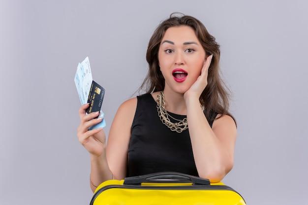 Jovem viajante surpresa, vestindo uma camiseta preta, segurando as passagens e o cartão de crédito, colocou a mão na bochecha sobre fundo branco