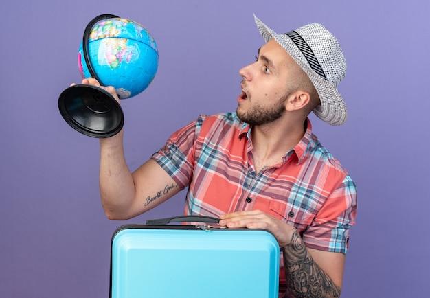 Jovem viajante surpreso com chapéu de palha de praia segurando e olhando para o globo em pé atrás da mala, isolado na parede roxa com espaço de cópia