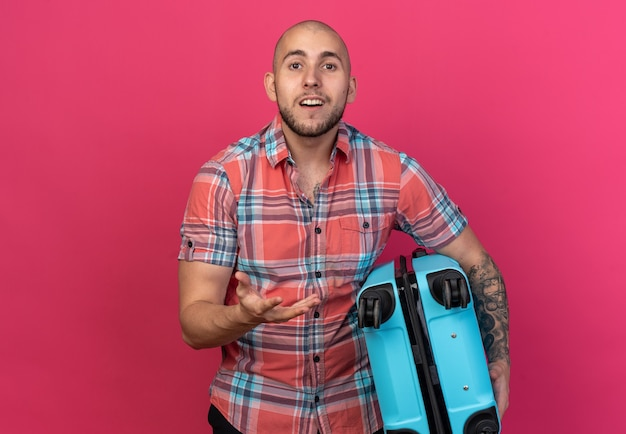 Jovem viajante surpreso segurando a mala e mantendo a mão aberta, isolada na parede rosa com espaço de cópia