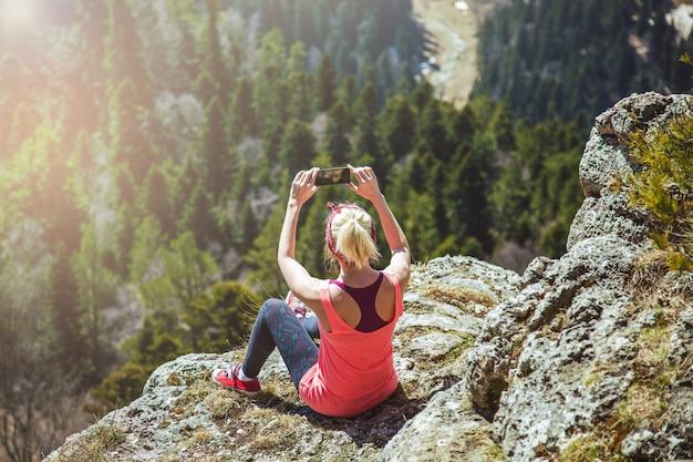 Jovem viajante tira fotos no smartphone bela vista da montanha. a menina adora viajar.