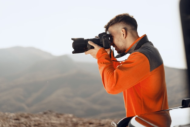 Jovem viajante tirando fotos de montanhas com câmera profissional