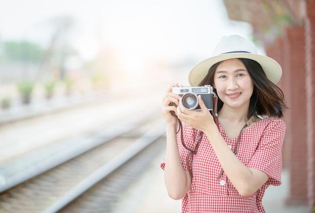 Jovem viajante tirar foto pela câmera vintage,