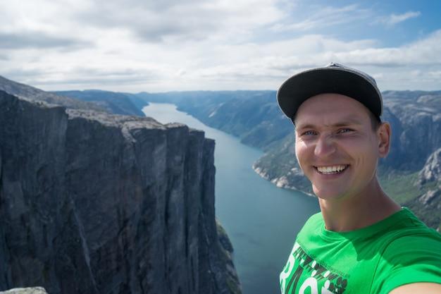 Jovem viajante tomando selfie no topo com lindo fiorde em fundo na noruega.